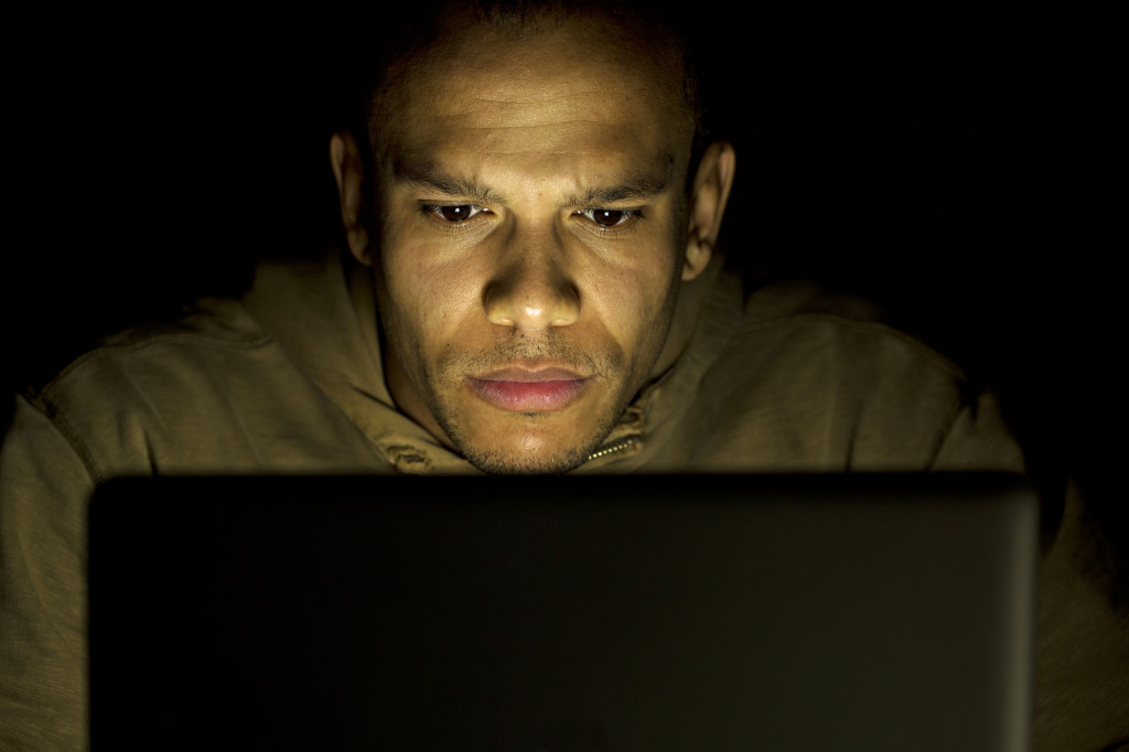 Man concentrating on his laptop at night